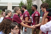 Participant Trey Fargis meets football players
