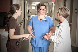 Barbato (left) and Underwood coordinate with another team member to devise the best plan of care for a patient.