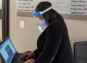 Staff at computer wearing face shield
